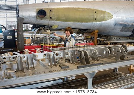 DAYTON, OHIO, USA-NOVEMBER 18, 2016:Tour guide at National Museum USAF, shown here in restoration hanger, points out parts to be used in the restoration of Boeing B-17D, The Swoose, in background.