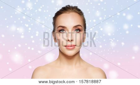 beauty, people, winter and health concept - beautiful young woman face over rose quartz and serenity gradient background and snow