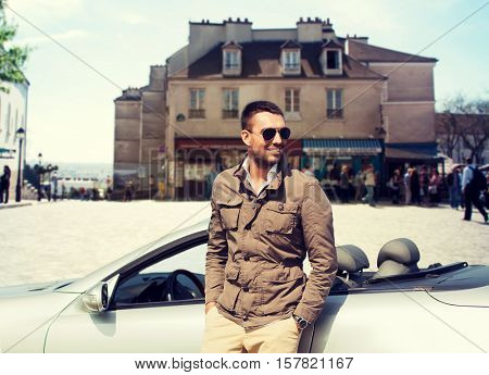 travel, tourism, road trip, transport and people concept - happy man near cabriolet car over city background