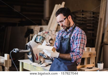 Handsome carpenter in protective glasses standing near his wooden object in the workshop.