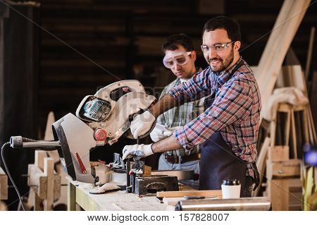 Two carpenters cutting a wooden plank with a circular saw.