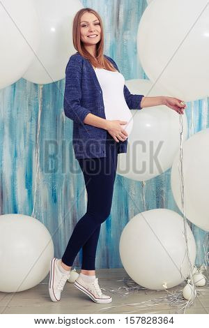 Full-length side view portrait of elated pregnant woman posing in studio surrounded with big round white balloons. Low angle of pregnant woman posing in studio