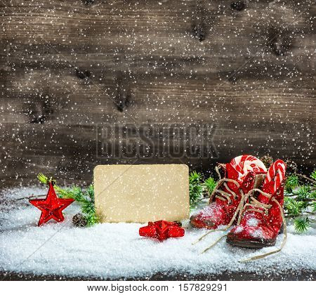 Vintage style Christmas decoration red stars and antique baby shoes. Retro postcard. Falling snow effect
