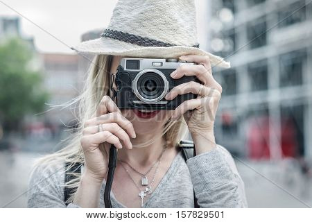 Woman photographer. Young female in hat with photo camera on the street in downtown Paris City  under sunlight at day time.