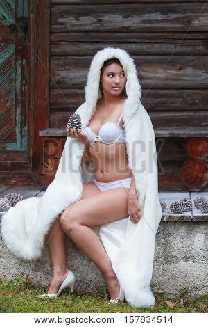 Young woman sitting in your underwear with white coat and a pine cone in his hand.