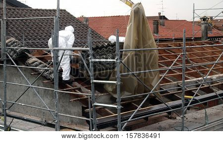 VAPRIO ITALY - NOVEMBER 7 2016: men at work on a roof of an old rural building removing asbestos panels