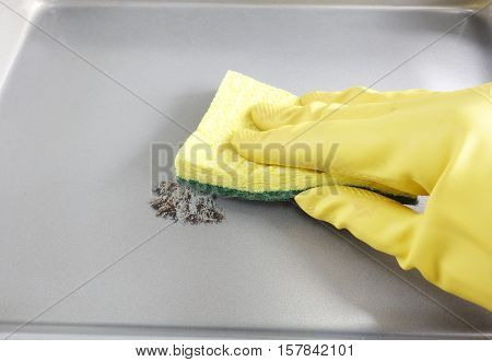 Person wearing a cleaning glove scrubbing a dirty pan