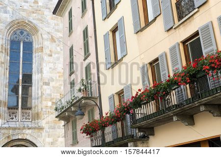Como (Lombardy Italy): exterior of the cathedral built from the 13th century and historic residential buildings with plants and flowers