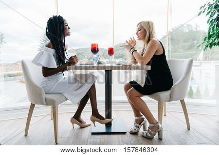 two beautiful women drinking alcohol in luxury restaurant. African and europian women are chatting. African girl is in white, blonde girl is in black dress. Blonde girl tell something to black woman and she is smiling.