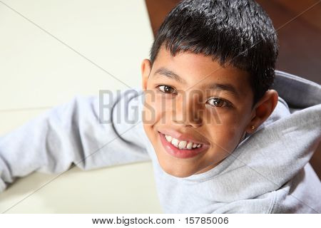 Smiling young ethnic school boy wearing grey hoodie in classroom