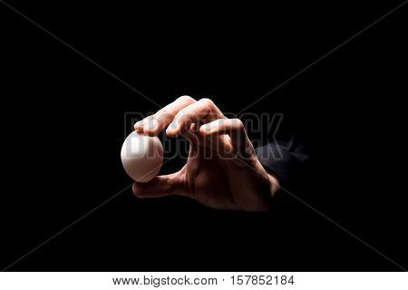 Demonstrate product. Close up of mans hand holding an egg while standing on black background and working in restaurant.