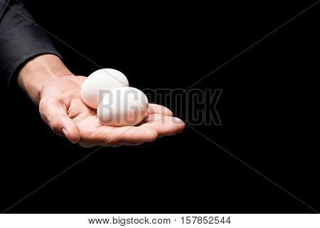 Natural ones. Close up of young mans hand holding two eggs while demonstrating them and standing on black background.