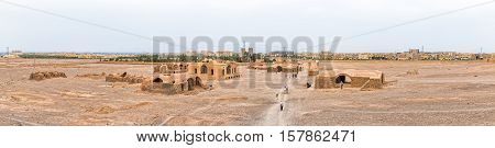 YAZD, IRAN - MAY 4, 2015: Panoramic view of the tourists sightseeing the Tower of Silence disused buildings at the foot of the hills.