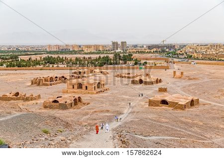YAZD, IRAN - MAY 4, 2015: Panoramic view of the tourists sightseeing the Tower of Silence disused buildings at the foot of the hills and new Zorastrian cemetery.