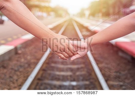 Woman Holding Her Daughter Hand At The Railway