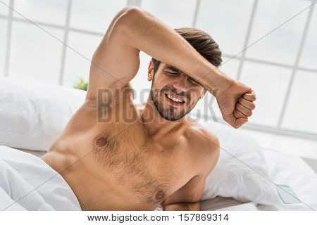 It hurts me so much. Frustrated young man is touching his head while suffering from pain. He is lying in bed
