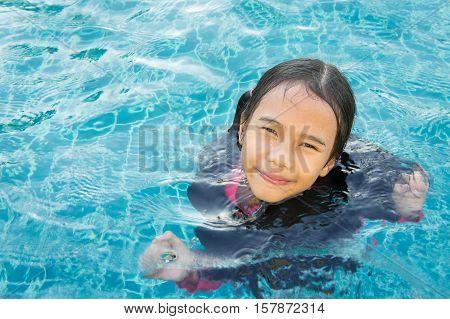 The baby girl asian enjoy swiming kid girl playing swiming young girl so cute swiming pool
