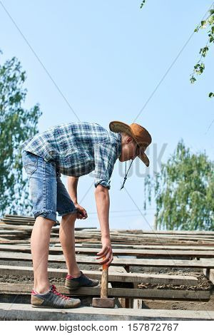 A young man with a hammer standing on the roof of an unfinished barn