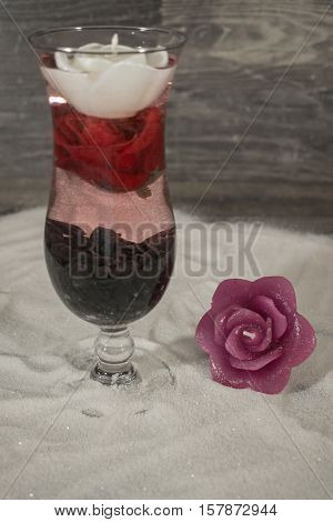 A candle in the rose design and a cocktail glass is located on the sand. The cocktail glass is decorated with black stones a rose and a floating candle