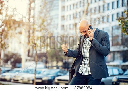 Businessman on the street receiving good news over the phone