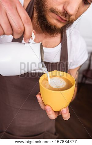 Man pouring milk into coffee while creating picture. He is standing in coffeehouse and looking at liquid with inspiration