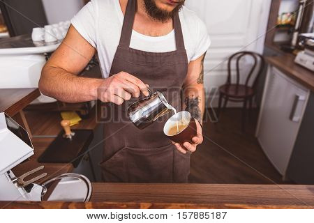 Skillful male bartender pouring milk into cup of coffee. He is standing in kitchen at coffeehouse