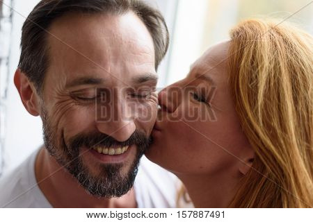 Be closer is always good idea. Close up of happy adult woman kissing male cheek with window on background