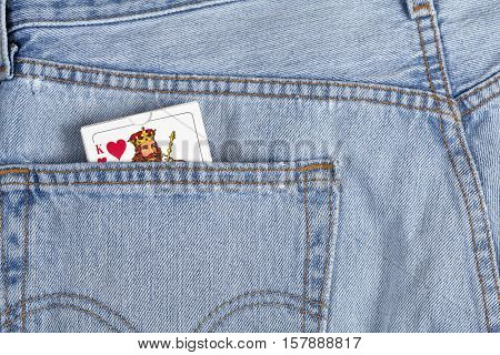 UMEA, SWEDEN ON DECEMBER 03, 2014. Illustration, a pair of blue jeans and a deck of cards in a pocket on December 03, 2014 in Umea, Sweden. Well used pants, Jack of hearts. Illustrative editorial.