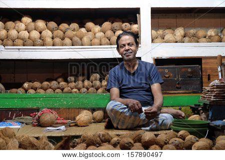 KOLKATA, INDIA - FEBRUARY 11: Indian vendor sits behind a large pile of skinned brown coconuts  in New Market in Kolkata on February 11, 2016.