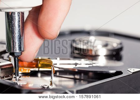 Closeup of a Hand Working on a Hard Disk Drive