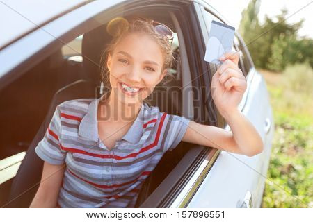 Portrait of Young Woman Showing Driver's License in her Car