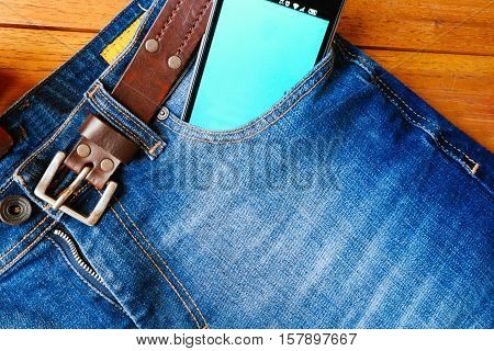 Jeans Trousers With Leather Belt And Smartphone In Pocket On Wooden Board