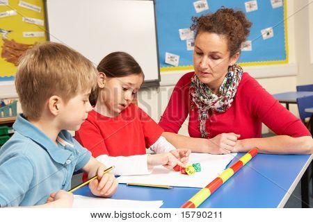School Children Studying In Classroom With Teacher