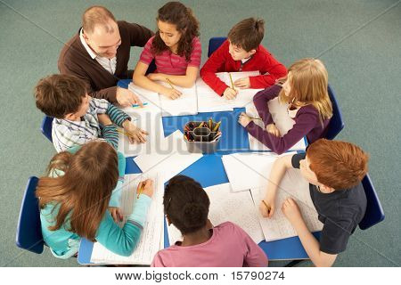 Overhead View Of Schoolchildren Working Together At Desk With Teacher
