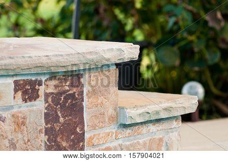 Tan and brown flag stone rock steps near garden.
