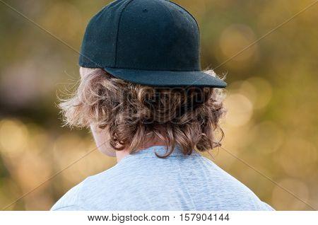 Teenage boy with long hair looking away in a black baseball hat.