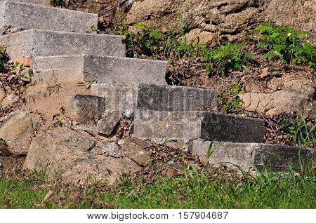 Old gray concrete stairs oudoor next to rock cliff