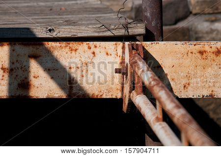 Rusted meal support pipe close up on the edge of an old wooden deck on a lake.