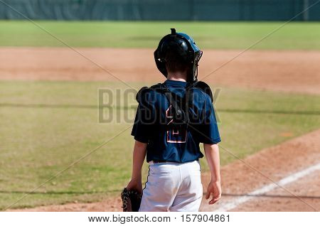 Young catcher with equipment on looking over at first base.