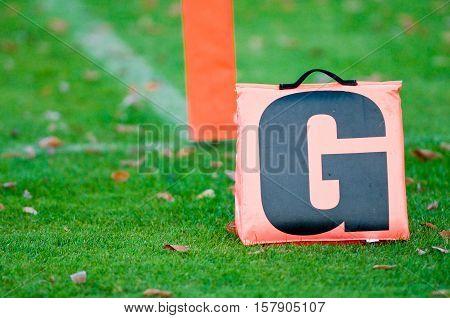 Orange football touchdown goal letter on a field.