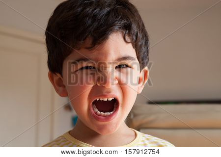Distressed boy shouting with mouth wide open