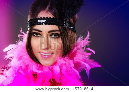 Retro flapper woman on carnival time. Young female pink plume and black feather on head.