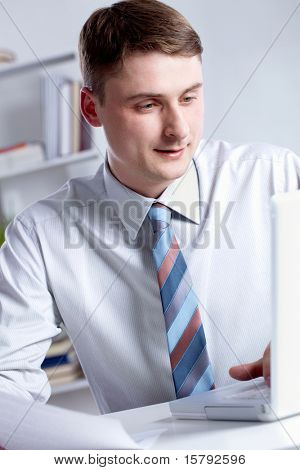 Portrait of serious manager looking at the laptop screen