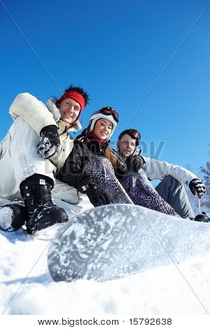 Portrait of happy company of guys and girl sitting on snow