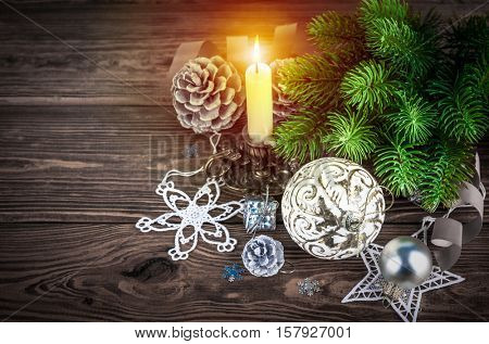 Christmas firtree with burning candle decoration pinecone holiday card new year still life on wooden boaard copyspace