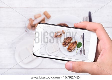 Hands taking photo spinach and feta stuffed chicken breast with smartphone.