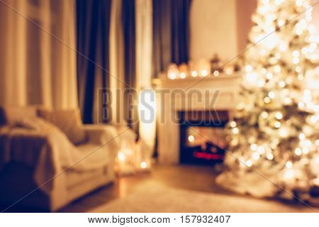 Beautiful holdiay decorated room with Christmas treem armchair and fireplace at night. Led lighting, cozy home scene. Nobody there. Out of focus shot for holiday background.