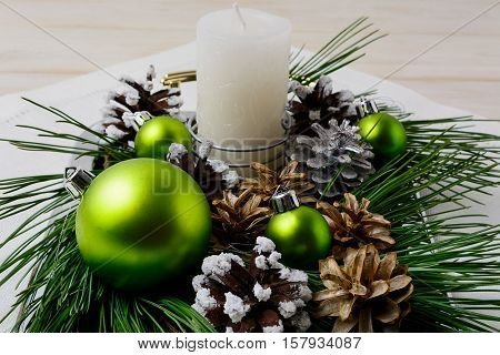 Christmas green ornaments and snowy pinecone decoration. Christmas background with shiny balls.