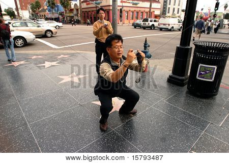 Asian tourist taking a picture with point and shoot camera at the Hollywood Blvd., L.A., California