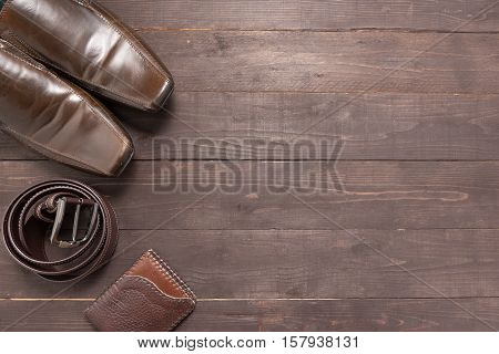 Elegant Set: Brown Wallet, Brown Men's Shoes, Brown Leather Belt, On The Wooden Background